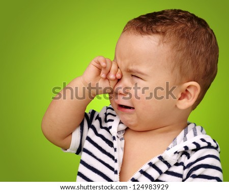Portrait Of Baby Boy Crying against a green background - stock photo