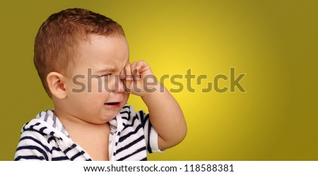 Portrait Of Baby Boy Crying against a yellow background - stock photo