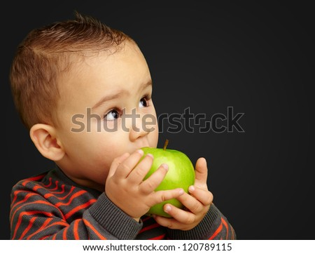 Portrait Of Baby Boy Eating Green Apple against a black background - stock photo