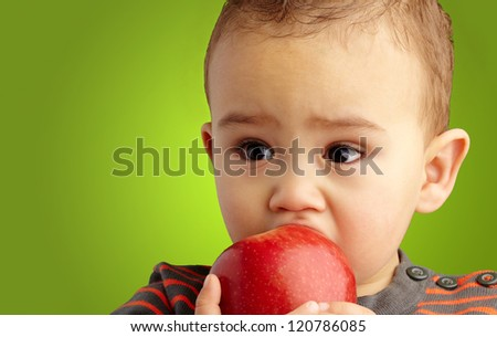 Portrait Of Baby Boy Eating Red Apple against a green background - stock photo