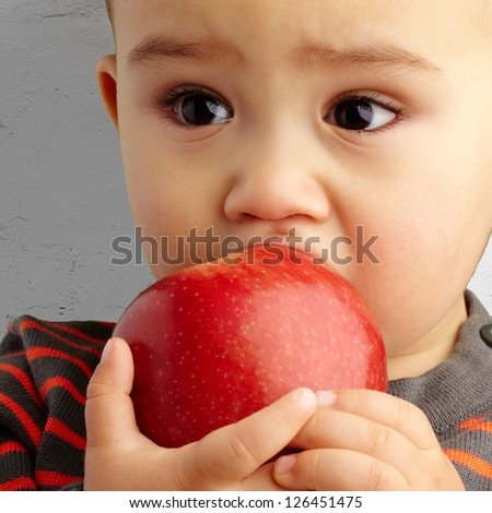 Portrait Of Baby Boy Eating Red Apple against a grunge background - stock photo