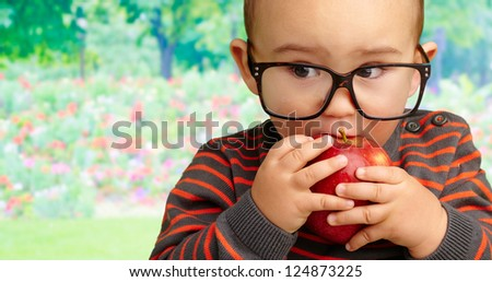 Portrait Of Baby Boy Eating Red Apple at a park, outdoor - stock photo