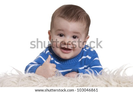 Portrait of baby boy giving thumbs up against white background - stock photo