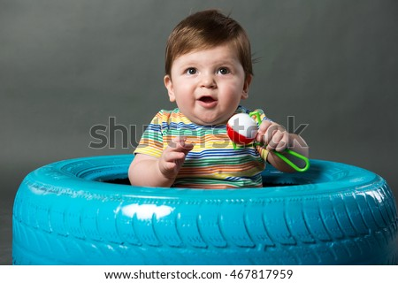 Portrait Of Baby Boy sitting in colored tyre against a grey background