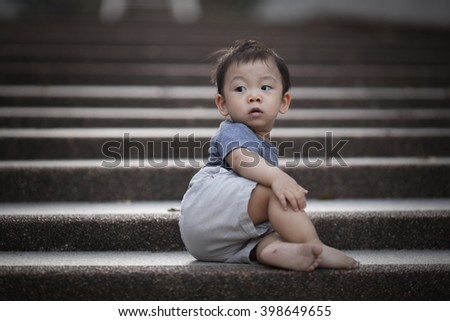 Portrait of baby boy sitting on stone stair at thai temple - stock photo