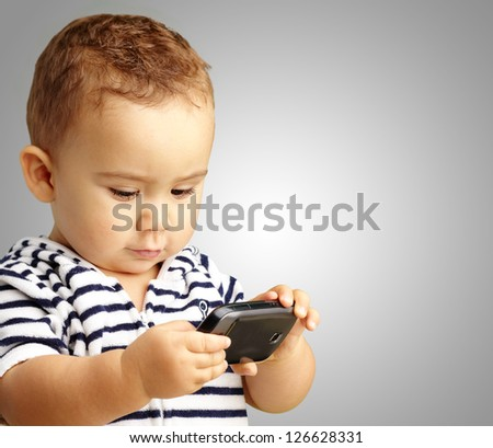 Portrait Of Baby Boy Using Cell Phone against a grey background - stock photo
