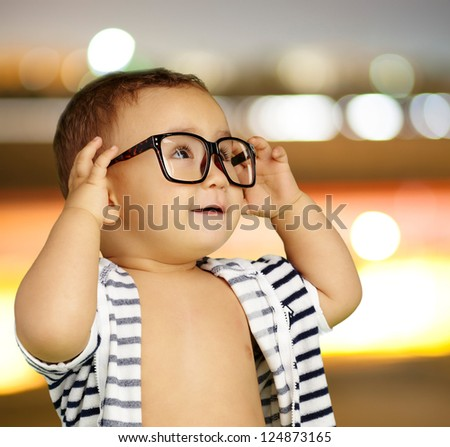 Portrait Of Baby Boy Wearing Eyeglasses against a city by night - stock photo