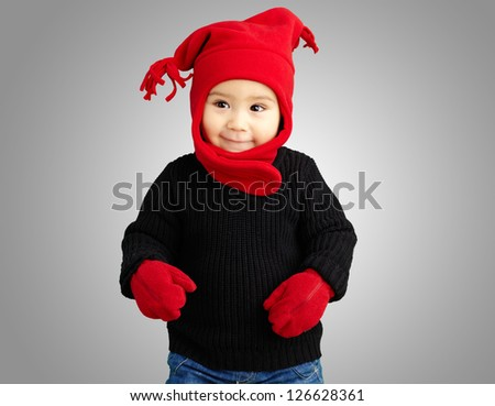 Portrait Of Baby Boy Wearing Warm Clothing against a grey background - stock photo