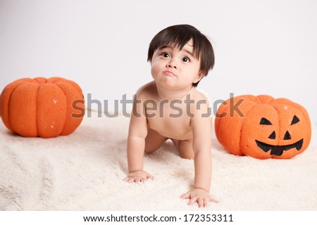 Portrait of baby boy with pumpkin - stock photo
