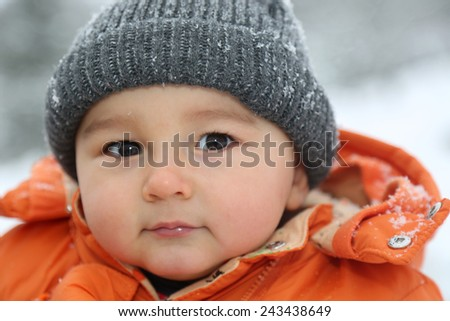 Portrait of baby boy with snow and cap in winter looking into camera - stock photo