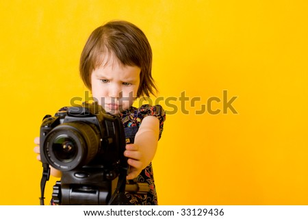 Portrait of baby girl holding photo camera isolated on yellow background - stock photo