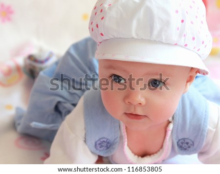 Portrait of baby girl in cap with blue eyes lying and looking. Closeup - stock photo