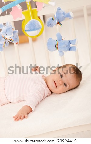 Portrait of baby girl in infant bed with toy bear.? - stock photo