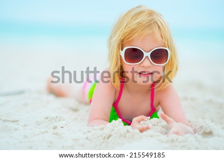 Portrait of baby girl in sunglasses laying on beach - stock photo