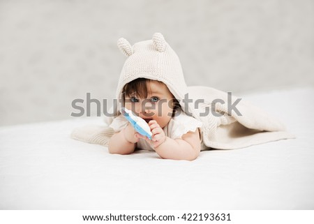 Portrait of baby girl playing with toy on blanket at home - stock photo