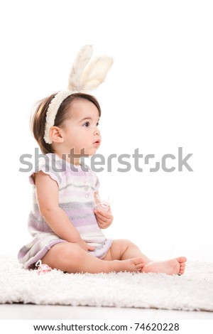 Portrait of baby girl with bunny ears headband, playing with easter eggs, isolated on white background.? - stock photo