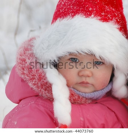 Portrait of baby in red hat in winter time - stock photo