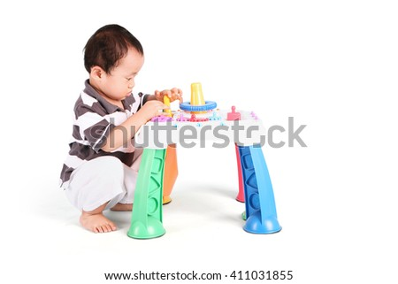 Portrait of baby playing with colorful toy, isolated on white background - stock photo