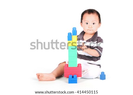 Portrait of baby playing with lego while sitting in studio, isolated on white background