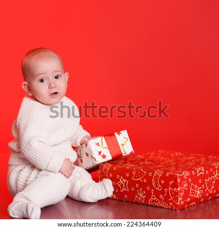 Portrait of baby wearing trendy knitted sweater, open christmas presents over red - stock photo