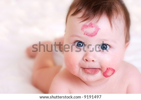 portrait of baby with kisses on his face - stock photo