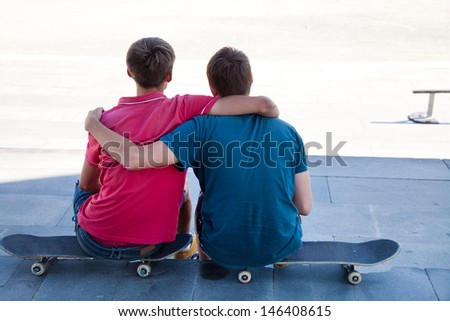 Portrait of back two friends skateboarders on the street - stock photo