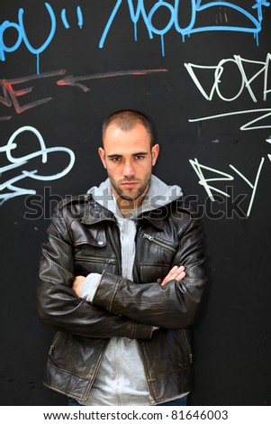 Portrait of bad boy standing on tagged wall - stock photo