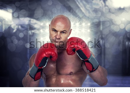 Portrait of bald boxer in red gloves against red boxing area with punching bags - stock photo