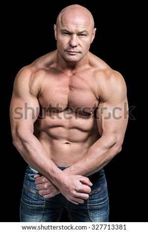 Portrait of bald man flexing muscles against black background - stock photo