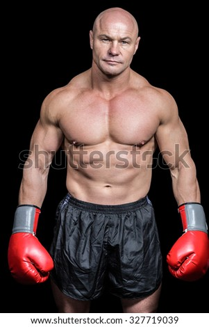Portrait of bald man with boxing gloves against black background - stock photo