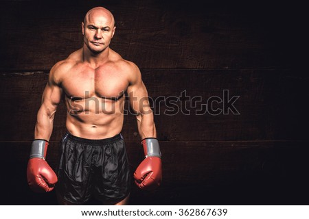 Portrait of bald man with boxing gloves against black wood - stock photo