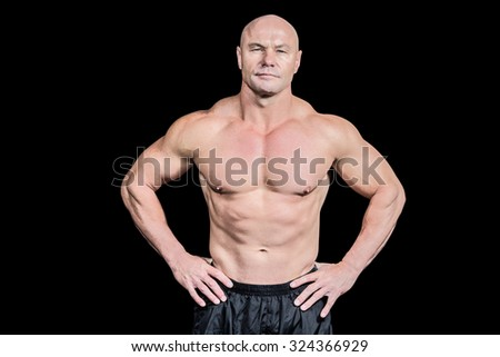 Portrait of bald man with hand on hip standing against black background - stock photo