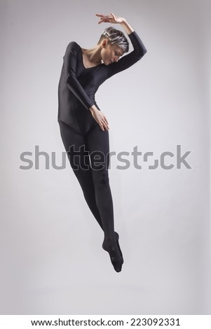 Portrait of ballet dancer who is dancing in dark clothes. Isolated in gray background