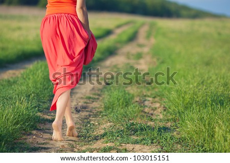 Portrait of barefoot woman in long red dress walking on the road in the green field in summer - stock photo