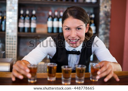 Portrait of bartender placing shot glasses in a row on bar counter in bar