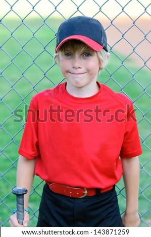 Portrait of baseball boy leaning on fence. - stock photo