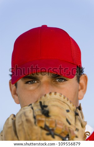 Portrait of baseball pitcher with glove - stock photo