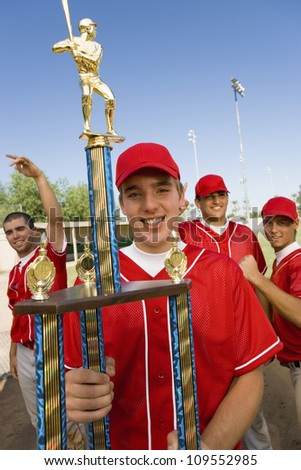 Portrait of baseball player holding trophy team-mates in background - stock photo