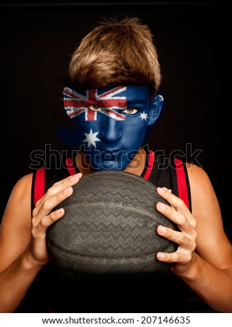 portrait of basketball player with australian flag painted on his face - stock photo