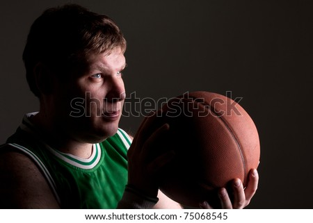 Portrait of basketball player with ball aiming to basket - stock photo