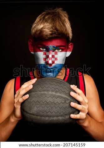 portrait of basketball player with croatian flag painted on his face - stock photo