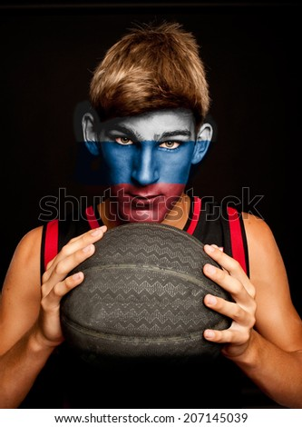 portrait of basketball player with russian flag painted on his face - stock photo