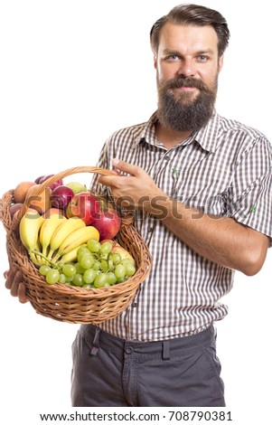 Portrait of bearded man holding basket of fruits against white background
