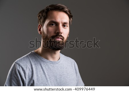 Portrait of bearded man in grey shirt looking at the camera on dark grey background - stock photo