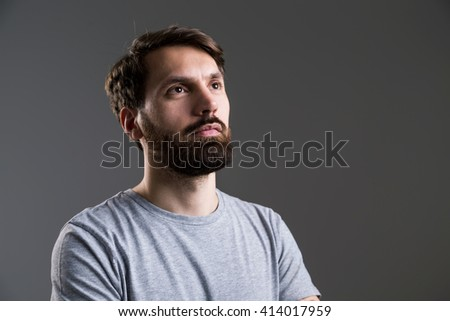 Portrait of bearded man in grey shirt looking away from the camera on dark grey background - stock photo