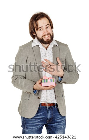 portrait of bearded man opening a surprise gift in a pink box with a bow with a look of joyful anticipation as he celebrates Christmas or his birthday.  - stock photo
