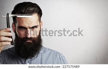 Portrait of bearded man with vintage straight razor - stock photo