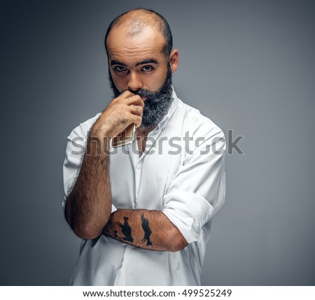 Portrait of bearded mix race male in a white shirt isolated on grey background.