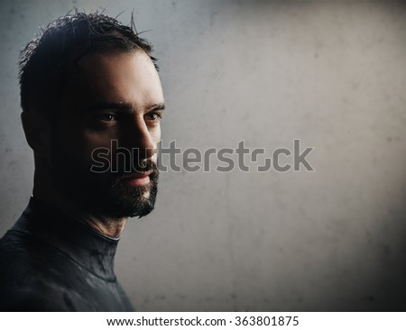 Portrait of bearded surfer on concrete background