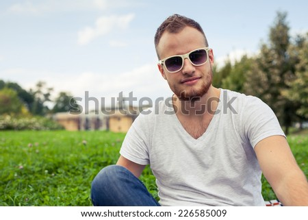 Portrait of bearded young man. Caucasian man smiling happy on sunny summer or spring day outside in park. - stock photo